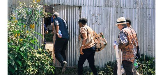 Researchers entering a door to visit a company in Addis Ababa, Ethiopia